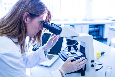 investigador cientifico: Científico que trabaja con un microscopio en el laboratorio de la universidad Foto de archivo