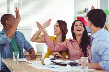 Papier de lancer de l'équipe créative dans l'air dans le bureau occasionnel Banque d'images