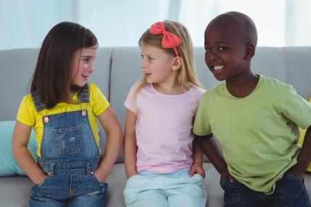 kanapa: Happy kids sitting together on the couch Zdjęcie Seryjne