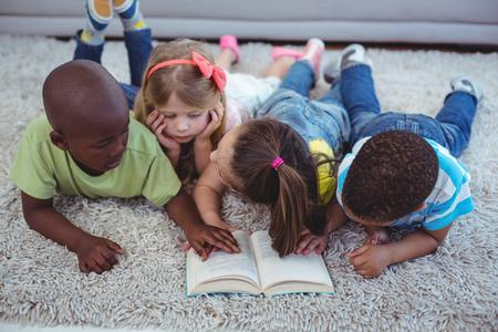 niños sentados: Felices los niños que leen un libro juntos en el suelo Foto de archivo