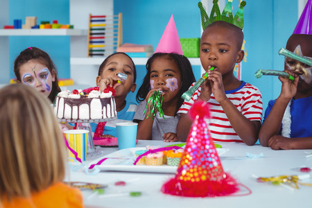 black color: Happy kids celebrating a birthday with cake Stock Photo