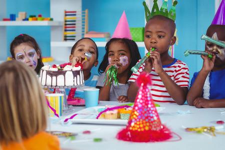children party: Happy kids celebrating a birthday with cake Stock Photo