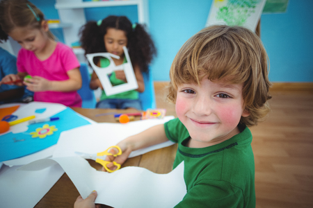 child: Happy kids doing arts and crafts together at their desk