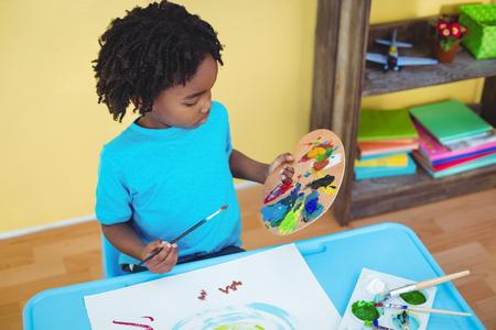 niños con lÁpices: Niño que usa pinturas para hacer una imagen en una mesa Foto de archivo