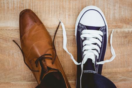 Blick auf zwei verschiedene Schuhe auf Holzbrett Lizenzfreie Bilder