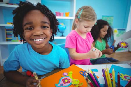 Enfants heureux à l'aide de pâte à modeler ensemble à leur bureau Banque d'images