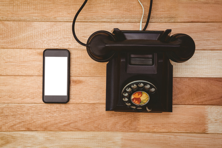 bakelite: View of an old phone and a smartphone on wood desk Stock Photo