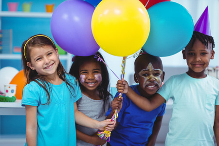 Happy kids with balloons at the birthday party