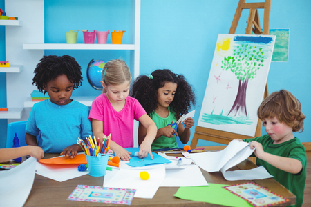 girls having fun: Happy kids doing arts and crafts together at their desk