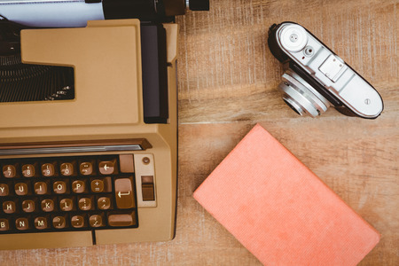 old desk: View of an old typewriter and camera on wood desk Stock Photo