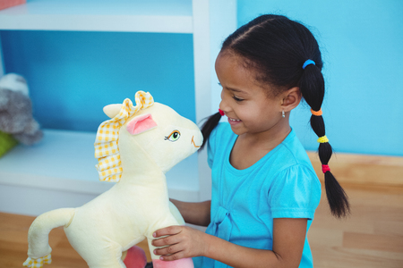 plushie: Small girl holding a pony teddy at their desk