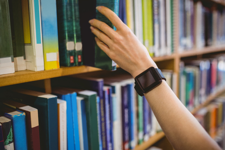 Student picking book in library wearing smart watch at the university