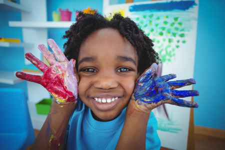 Happy kid enjoying arts and crafts painting with his hands Stock Photo