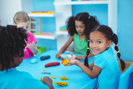 modelling clay: Smiling kids using modelling clay at their desk