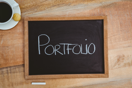 strong message: Portfolio against a big blackboard on wood desk