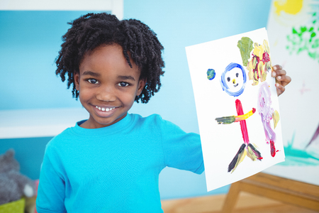 Happy kid enjoying arts and crafts painting at their desk Stock Photo - 47506616