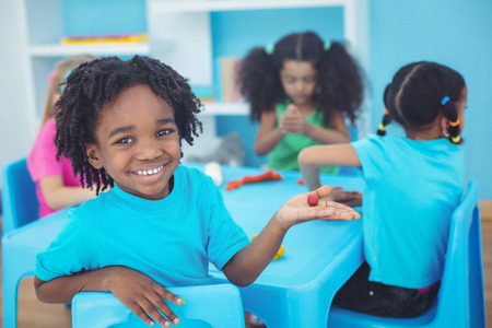 black color: Smiling kids using modelling clay Stock Photo