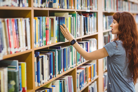 library: Mature student picking book in library wearing smart watch at the university Stock Photo