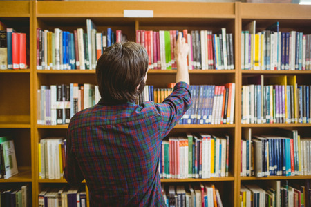 college campus: Student picking a book from shelf in library at the university