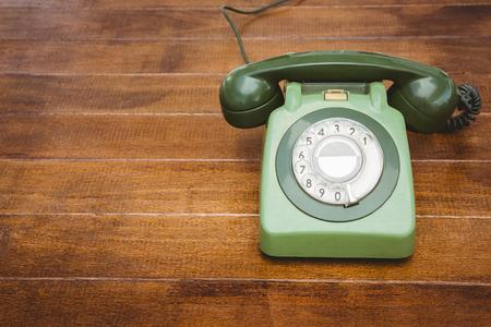 hablando por celular: Vista de un antiguo teléfono en el escritorio de madera