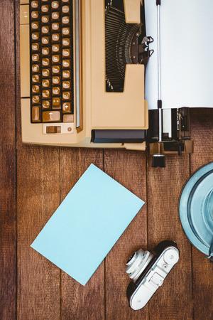 maquina de escribir: Vista de una vieja m�quina de escribir y la c�mara en el escritorio de madera Foto de archivo