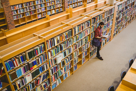 Student reading a book from shelf in library at the university