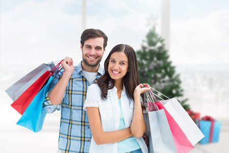house shopping: Happy couple with shopping bags against home with christmas tree Stock Photo