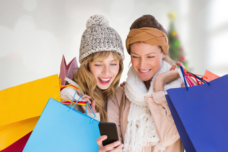 christmas shopping bag: Smiling women with shopping bags looking at mobile phone  against blurry christmas tree in room