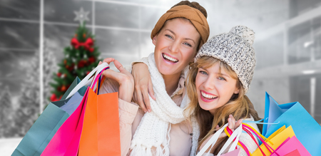 christmas shopping: Smiling women looking at camera with shopping bags  against home with christmas tree