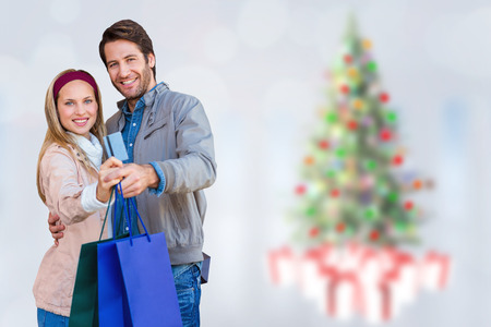 christmas shopping bag: Smiling couple showing credit card and shopping bags against blurry christmas tree in room Stock Photo
