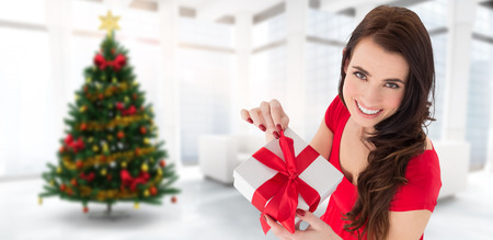 opening gift: Happy brown hair opening gift  against home with christmas tree