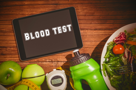 blood test: The word blood test against tablet on healthy persons table