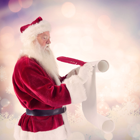 pere noel: Father Christmas writes a list against glowing christmas background Banque d'images