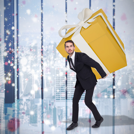 giant man: Stylish man with giant gift against glittering lights in room Stock Photo