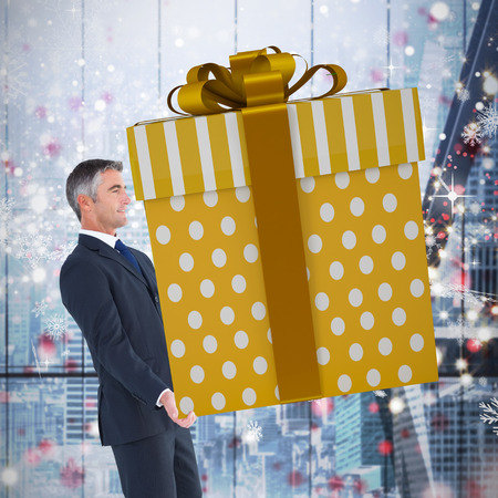 stylish men: Stylish man with giant gift against glittering lights in room Stock Photo