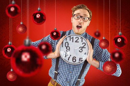 geeky: Geeky businessman holding a clock against red snowflake background