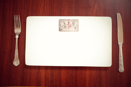 weighing scales: weighing scales against overhead view of burger with french fries and salad