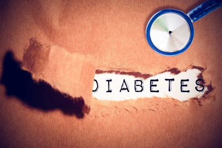 cut or torn paper: diabetes against close-up of damaged brown paper Stock Photo