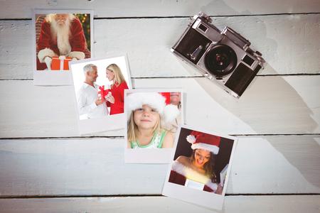 pere noel sexy: Sourire couple enlac� et tenant cadeau contre des photos instantan�es sur plancher en bois Banque d'images