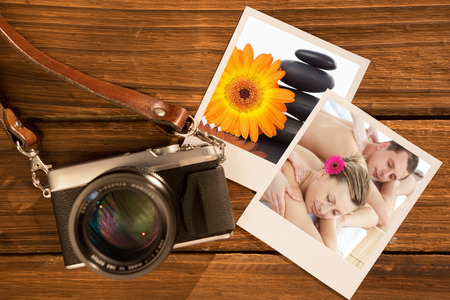 Relaxing couple having a massage  against lighted candles pebble stack an orange gerbera photo