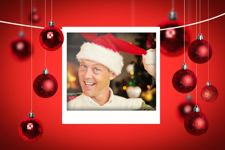 wearing santa hat: Christmas photographs against smiling man wearing santa hat Stock Photo
