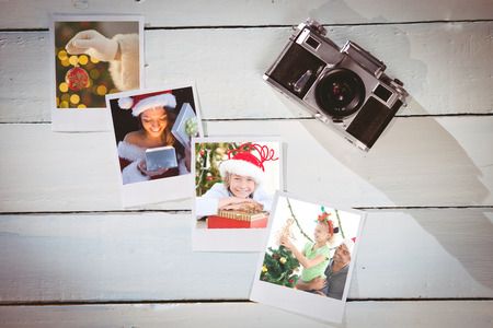 Pretty brunette in santa outfit opening gift against instant photos on wooden floor photo