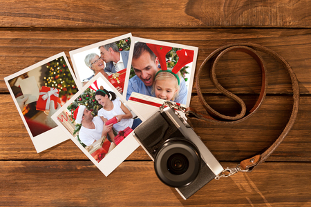 Senior man giving a kiss and a Christmas present to his wife against instant photos on wooden floor photo