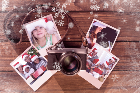 Girl wearing Santa hat at home against instant photos on wooden floor Stock Photo