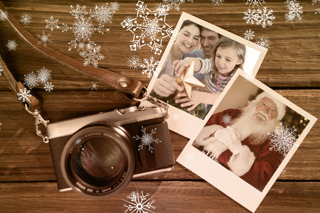 Family Christmas portrait against instant photos on wooden floor photo
