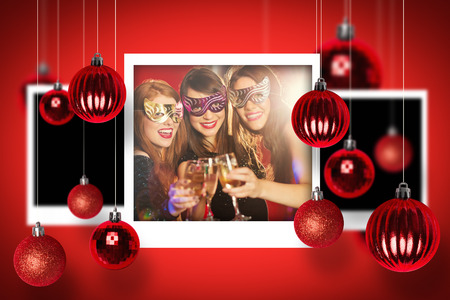 hedonistic: Christmas photographs against friends in masquerade masks toasting with champagne