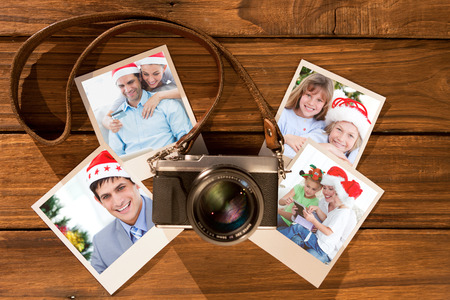Cute couple in santa hats shopping online with laptop against instant photos on wooden floor photo