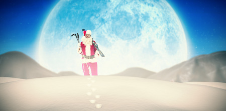 quaint: Santa claus holding ski and ski poles against quaint town with bright moon Stock Photo