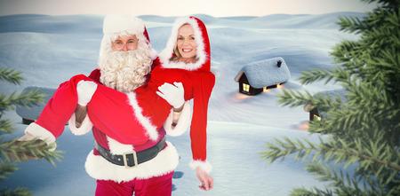señora: Santa y señora Claus sonriendo a la cámara contra el pueblo lindo en la nieve Foto de archivo