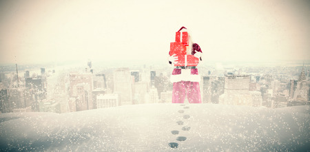 carrying: Santa carrying gifts against new york Stock Photo